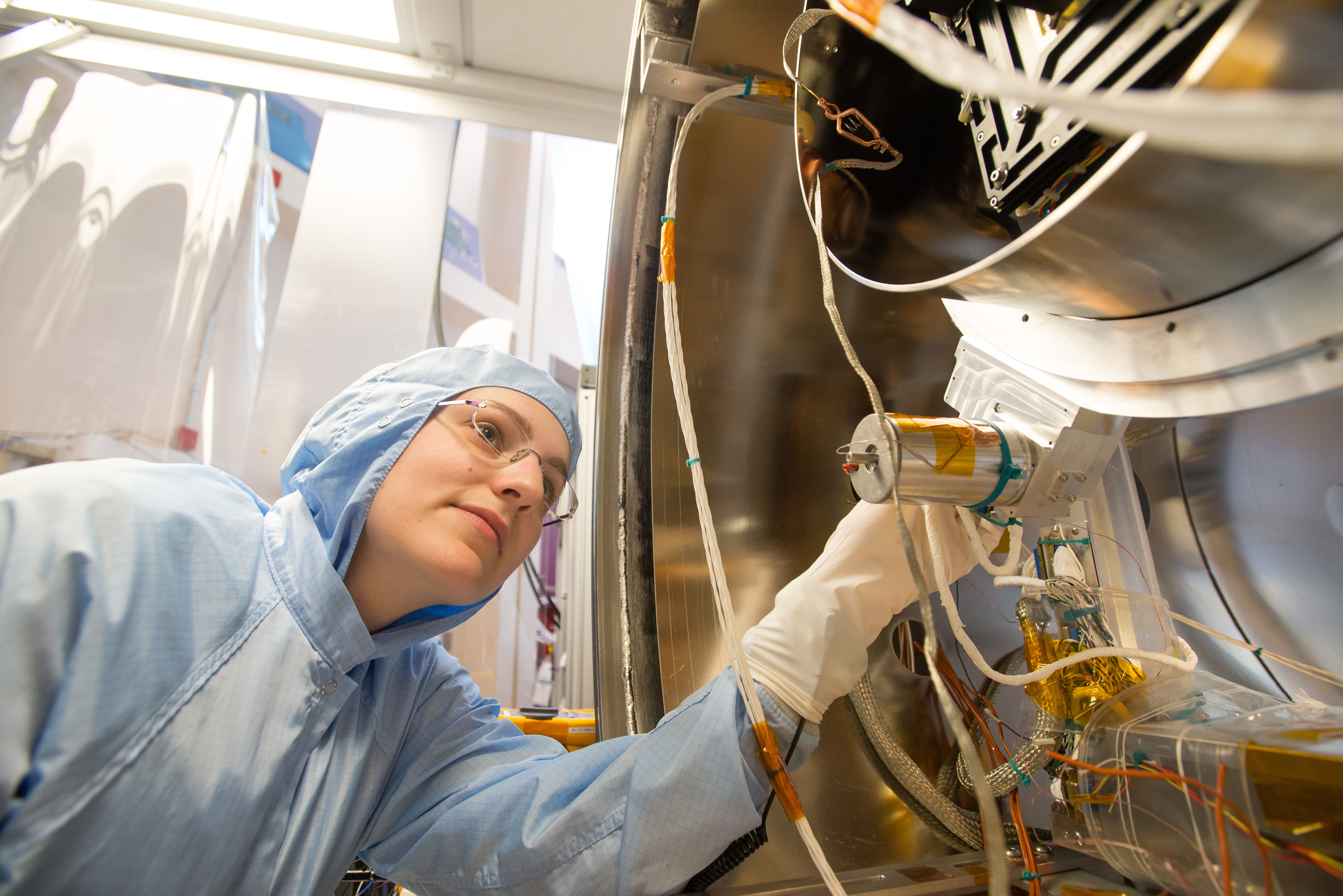 Woman wearing glasses and a blue Tyvek suit and white latex gloves inspects silver space instrument with wires coming out of it.