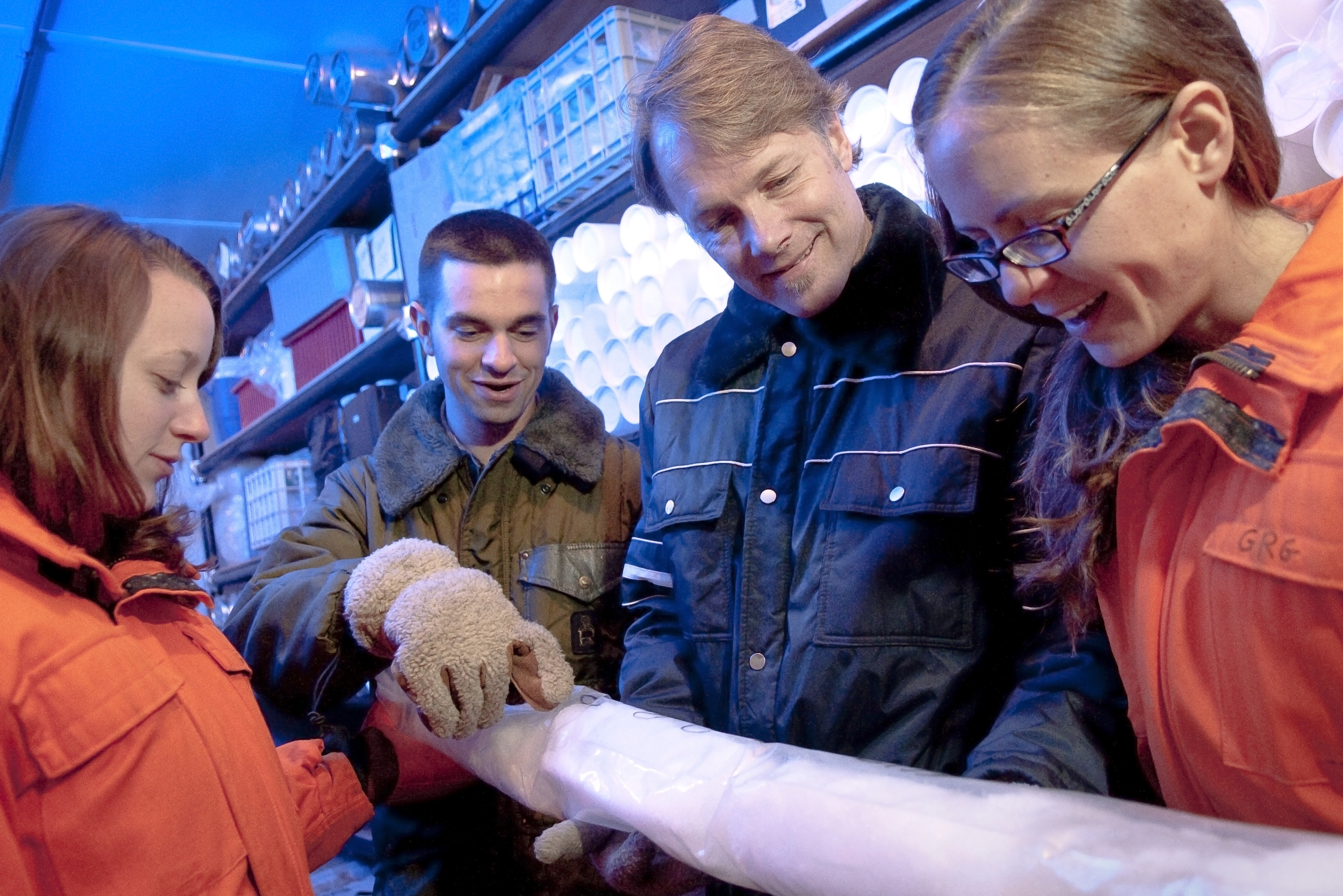 Two men and two women stand around an ice core they are holding while wearing very warm clothing.