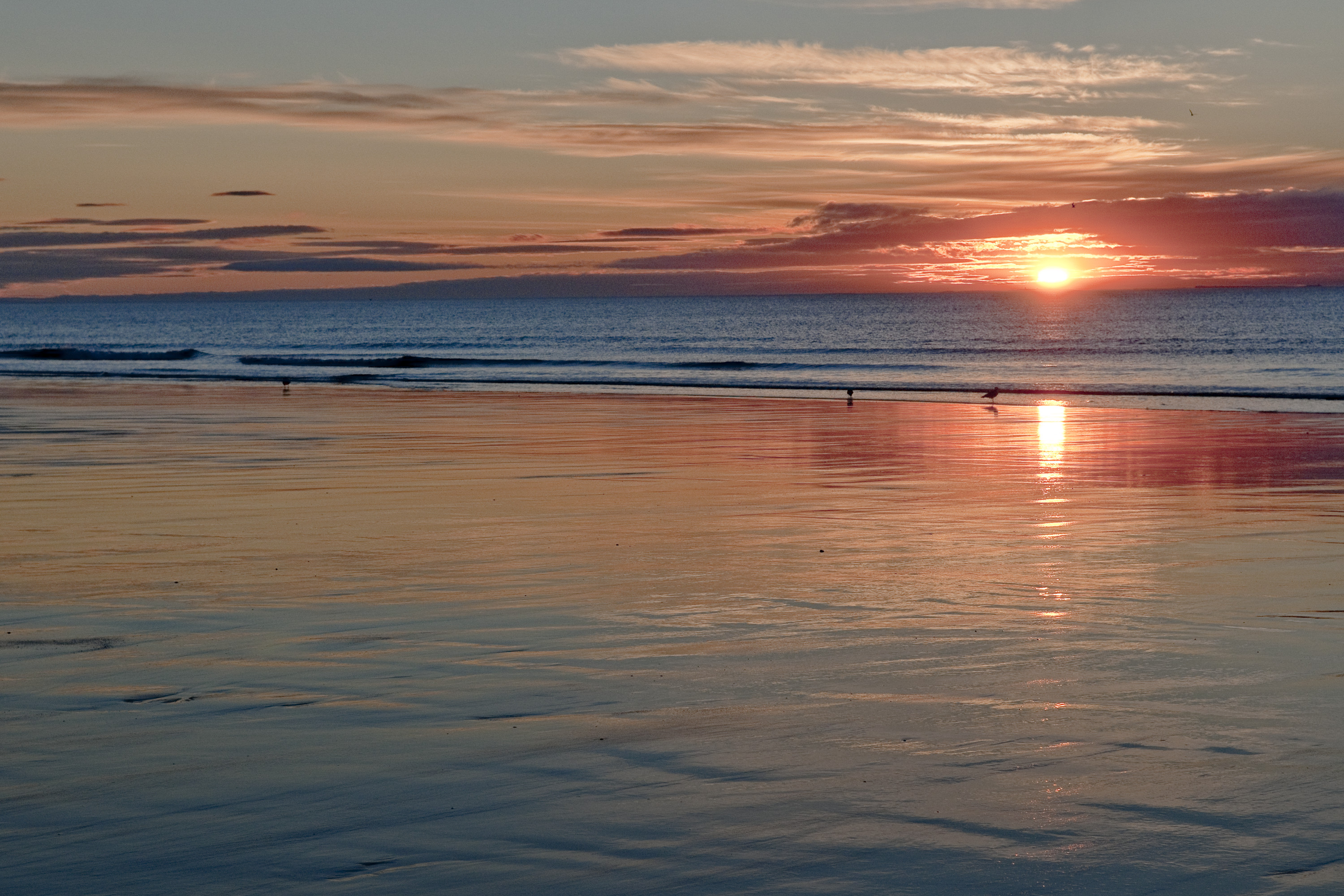 Sandy beach with sunrise in orange and yellow sky colors.