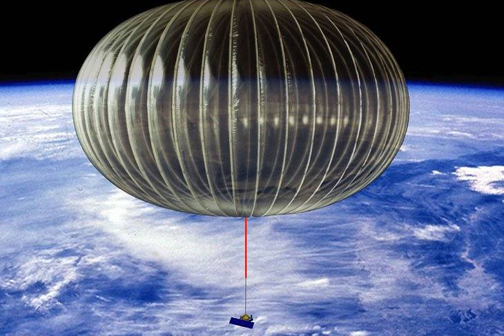 A scientific balloon is inflated carrying a small box in the upper atmosphere with the Earth way below.