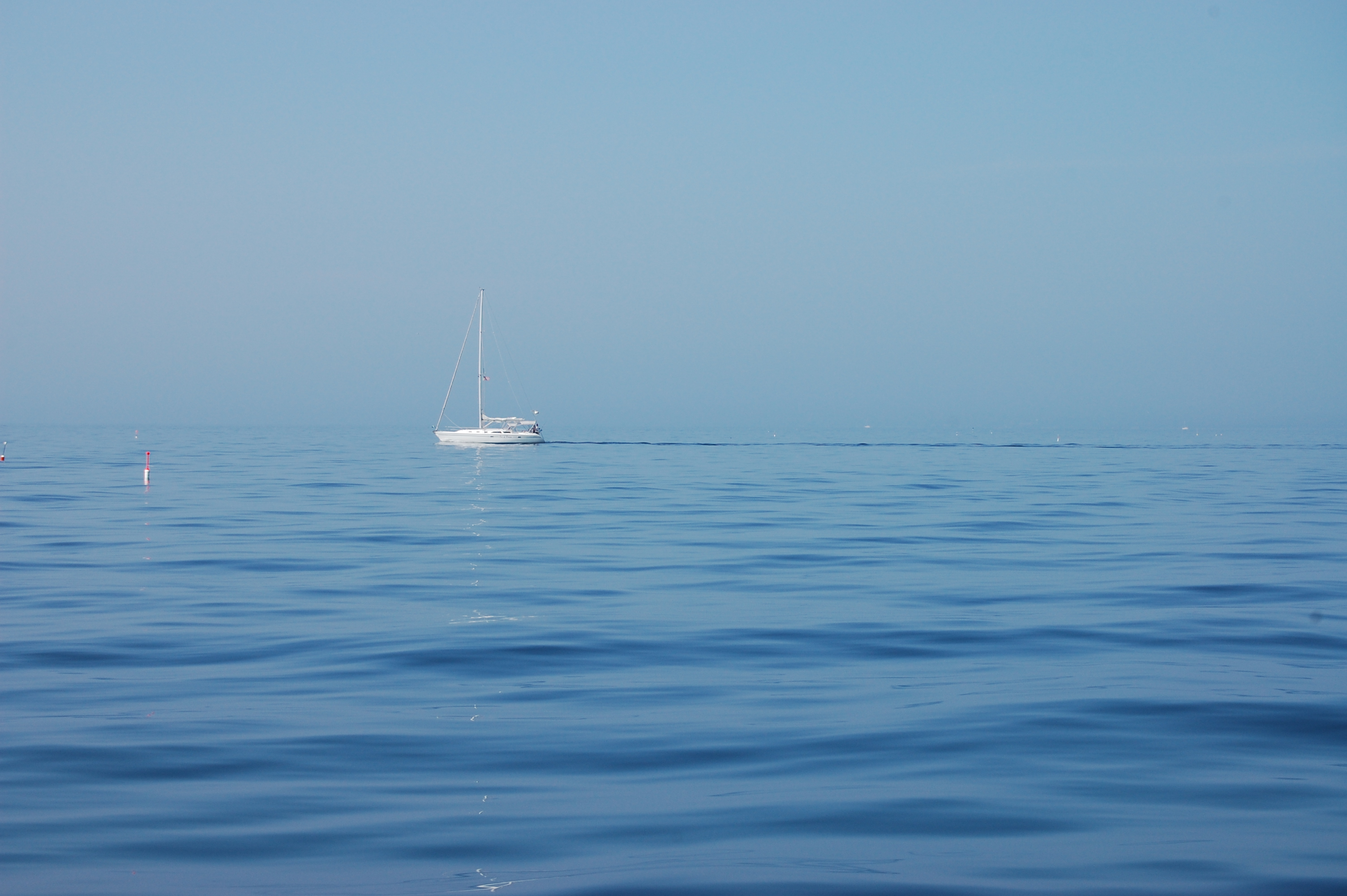 blue ocean with sailboat
