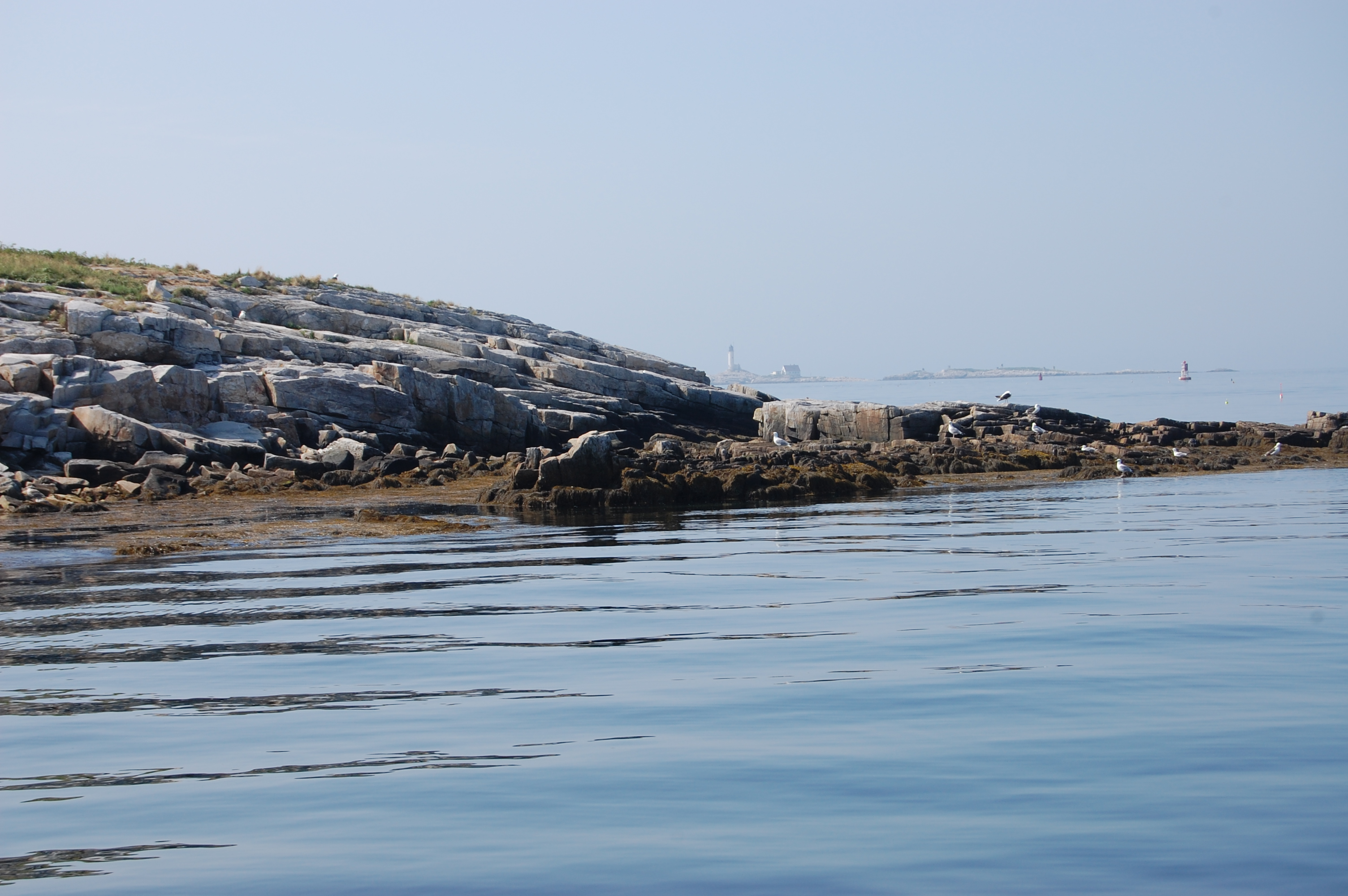 A rocky shoreline on a hazy summer day with calm seas.