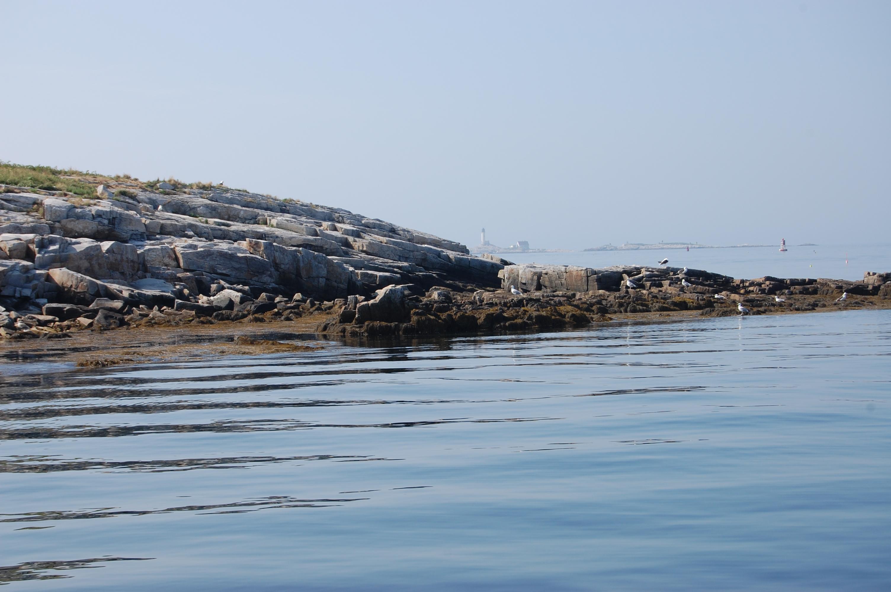 A rocky shoreline on a hazy summer day with calm seas.