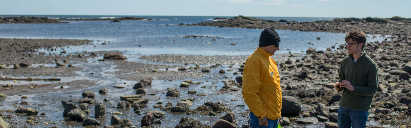 Two men stand on rocky shoreline