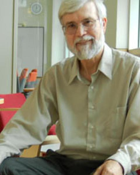An older man with white hair, beard, mustaches and glasses sits on a chair and gives a small smile for the camera.