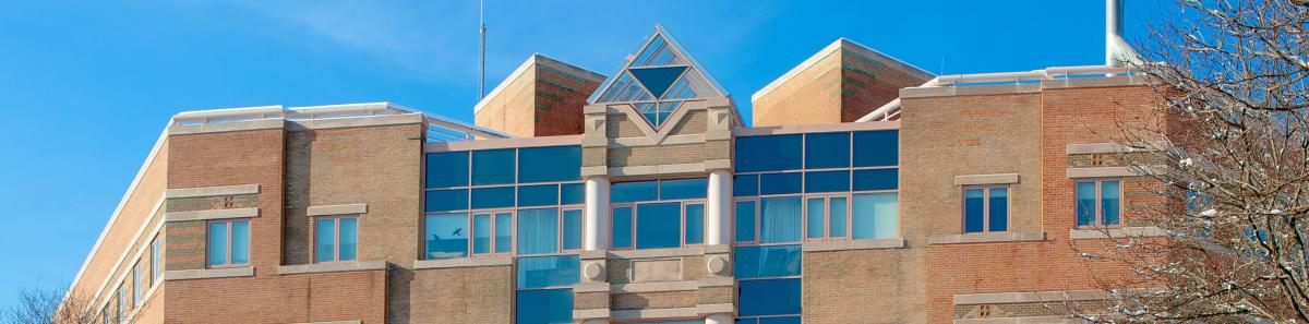A geometric building of brick and glass with blue skies behind it.