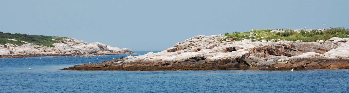 Two rocky islands are separated by a small segment of ocean.