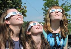 three girls viewing an eclipse