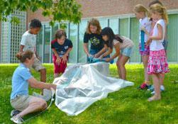 students and teacher conducting an experiment outdoors