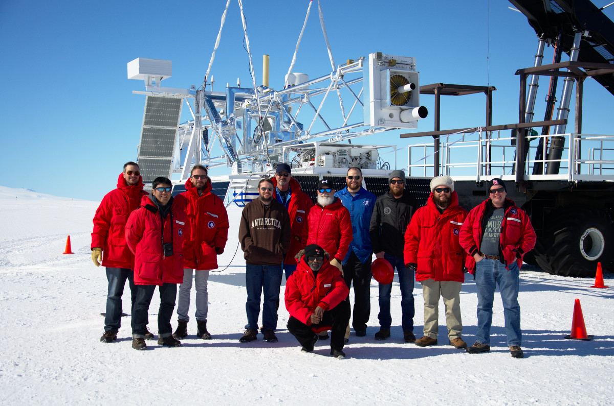 Group of people in Antarctica stand in front of large telescope.