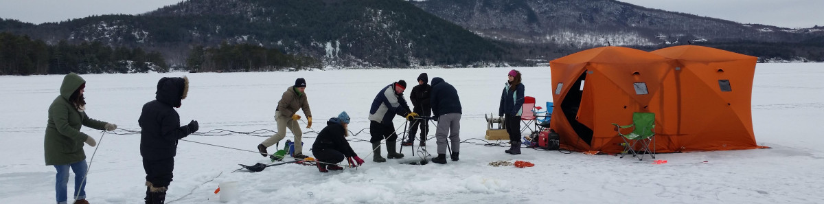 People in winter clothes stand on ice-covered pond lowing acoustic equipment under the water.